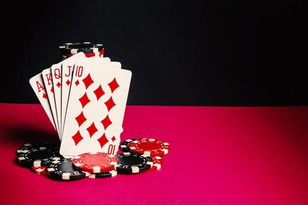 Pokerkaarten met royal flush combinatie. close-up van speelkaarten en chips in pokerclub. gratis advertentieruimte