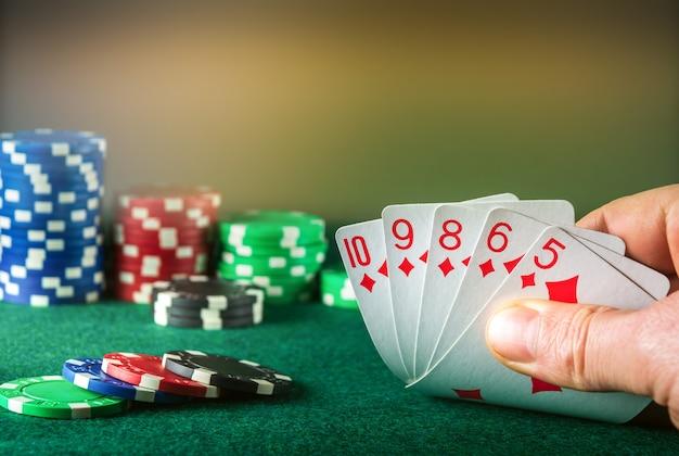 Pokerkaarten met straight flush combinatie. close up van gokker hand neemt speelkaarten in pokerclub
