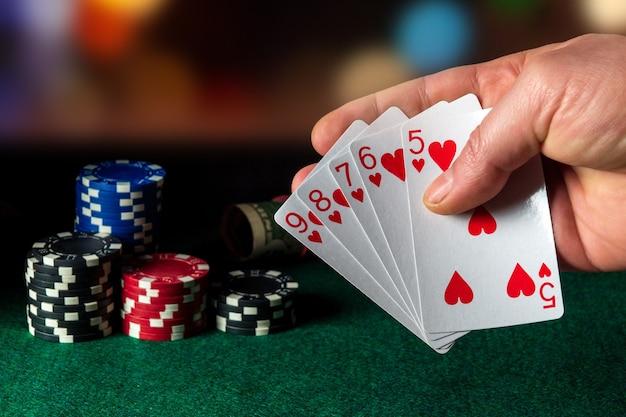 Pokerkaarten met straight flush combinatie in het spel. close-up van een gokker hand houdt speelkaarten in pokerclub. chips op groene tafel