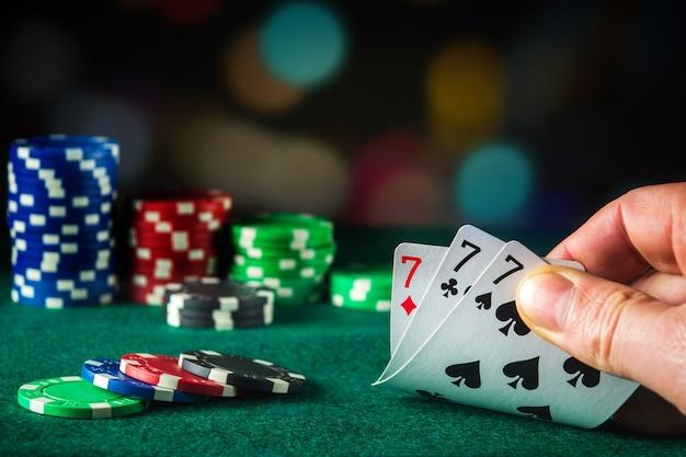 Pokerkaarten met three of a kind of vaste combinatie. close up van gokker hand neemt speelkaarten in pokerclub