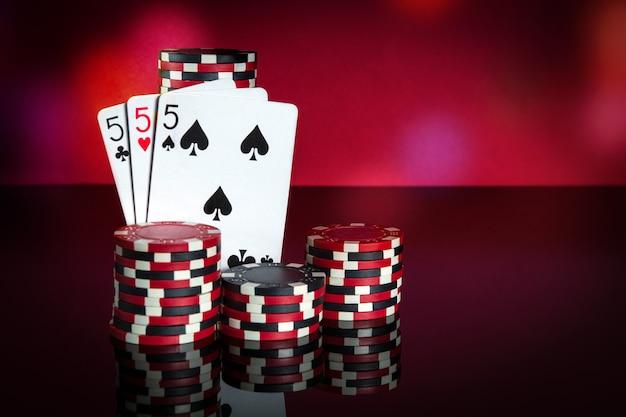 Pokerkaarten met three of a kind of vaste combinatie. close-up van speelkaarten en chips in pokerclub. gratis advertentieruimte