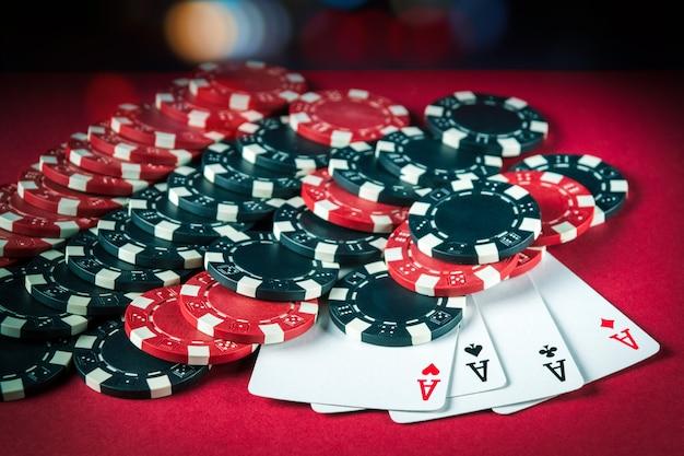 Pokerspel met four of kind-combinatie. chips en kaarten op de rode tafel. succesvolle en maximale winst