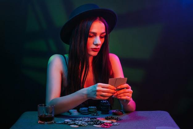 Pokerspeler aan een casinotafel met kaarten en chips. de vrouw met de hoed is aan het gokken