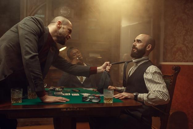 Pokerspeler greep de gelijkspel van zijn tegenstander, scherper in casino, risico. verslaving