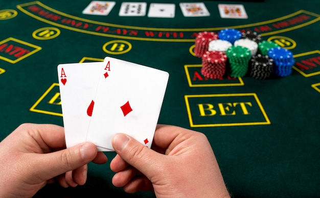 Pokerspeler houdt kaarten. first-person aanzicht. twee azen, een winnende combinatie. mannelijke handen