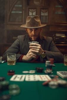 Pokerspeler in pak en hoed speelt in casino, risicoverslaving.