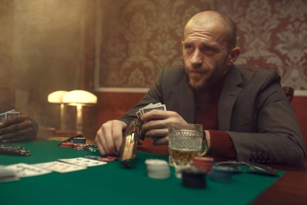 Pokerspeler met pistoolspelen in casino, risico. kansverslaving. man vrije tijd in gokhuis, speeltafel met groene doek