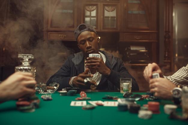 Pokerspelers aan speeltafel met weddenschappen. kansverslaving, risico, gokhuis. mannen vrije tijd met whisky en sigaren