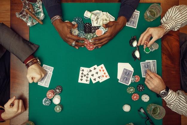 Pokerspelers handen met kaarten, bovenaanzicht, speeltafel met groene doek in casino