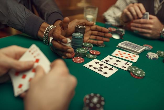 Pokerspelers handen met kaarten, speeltafel met groene doek in casino