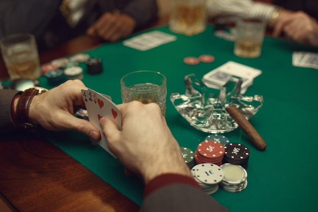 Pokerspelers zitten aan de tafel met kaarten en chips in casino in