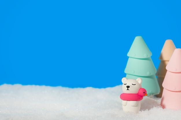 Polar speelgoed beer met kerstbomen in de sneeuw op blauw.