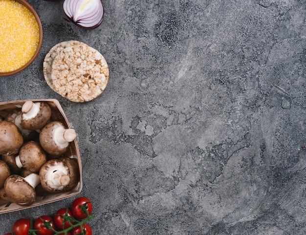 Polenta kom; ui; gepofte rijst cake; champignons en cherrytomaatjes op grijze betonnen achtergrond