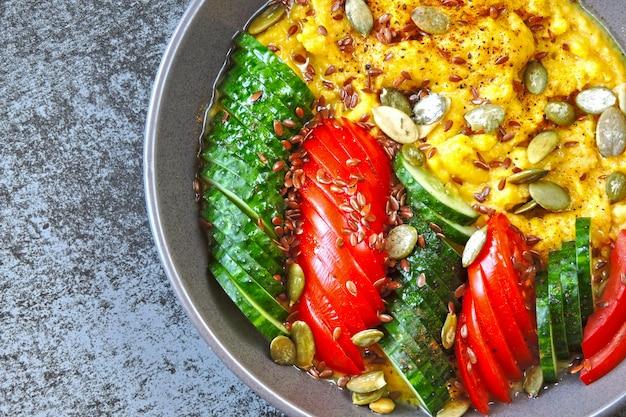 Polenta met groenten. maïspap met groenten. veganistische lunchkom met maïspap. veganistische polentameel, groenten, lijnzaad en pompoenpitten.