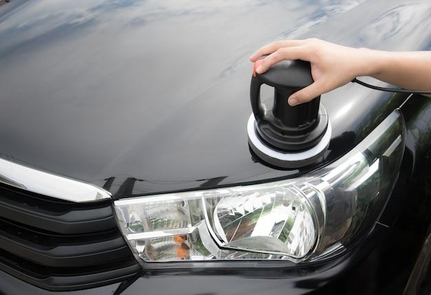 Polijsten van de zwarte auto met polijstmachine in de garage
