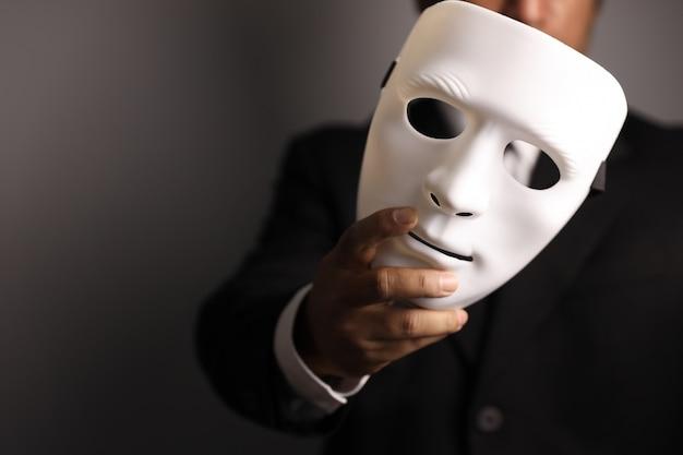 Politicus of zakenman die zwart kostuum draagt en wit masker toont