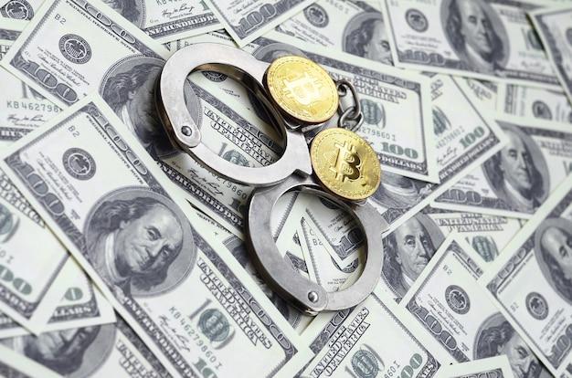 Politie handboeien en bitcoins liggen op een groot aantal dollarbiljetten.