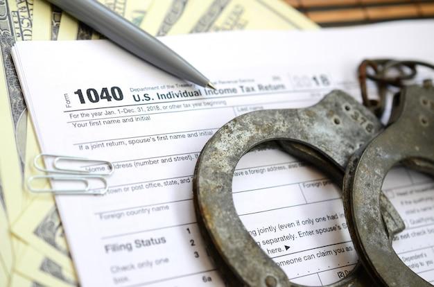 Politie handboeien liggen op het belastingformulier 1040. het concept van problemen met de wet in de nasleep van niet-betaling van belastingen
