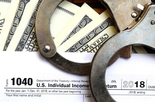 Politie handboeien liggen op het belastingformulier 1040. het concept van problemen met de wet