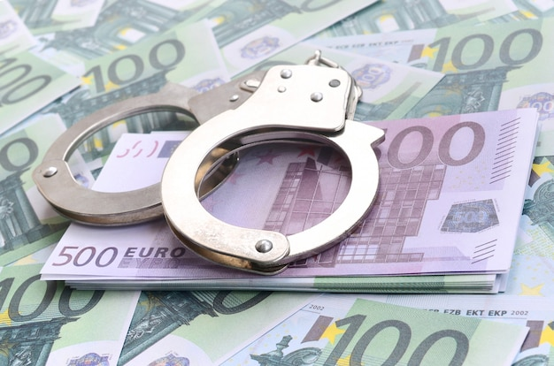 Politie handboeien ligt op een set van groene monetaire coupures van 100 euro. veel geld vormt een oneindige hoop