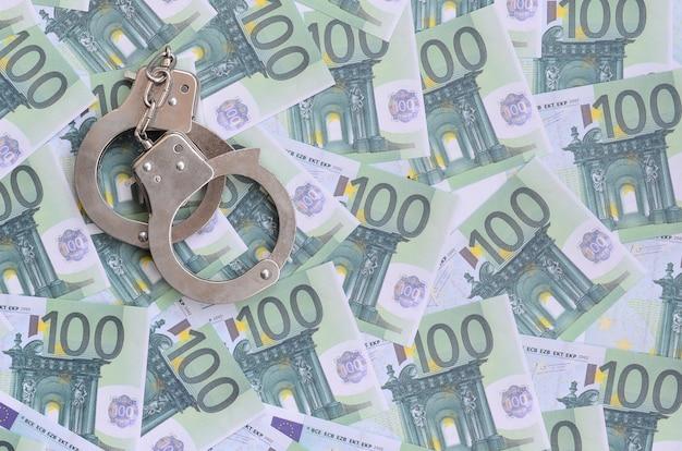 Politie handboeien ligt op een set van groene monetaire coupures van 100 euro