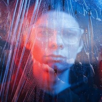 Politie kleuren. studio opname in donkere studio met neonlicht. portret van ernstige man achter het natte glas