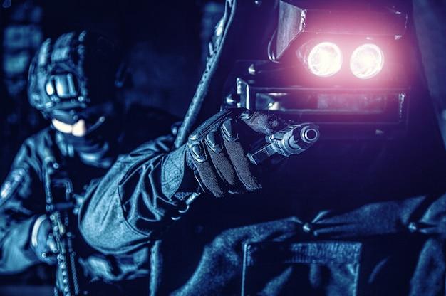 Politie teamlid met speciale wapens en tactieken gericht met een pistool wanneer hij door het raam in ballistisch schild kijkt, kameraad achter hem beschermt, weg verlicht, vijanden verblindt met fel licht 's nachts