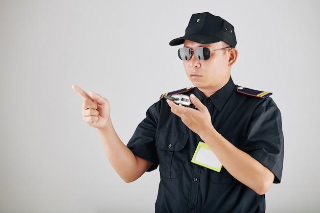 Politieagent die politieradio gebruikt