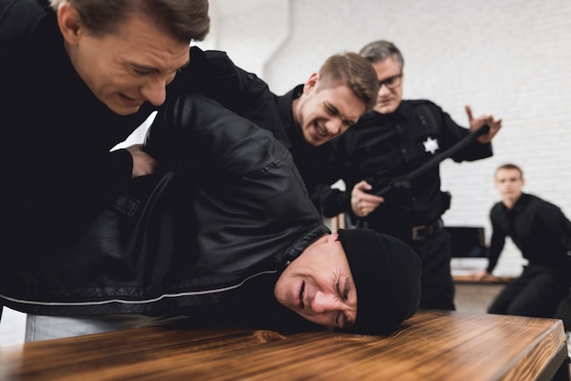 Politieagent duwde de crimineel tegen de tafel en houdt hem vast.