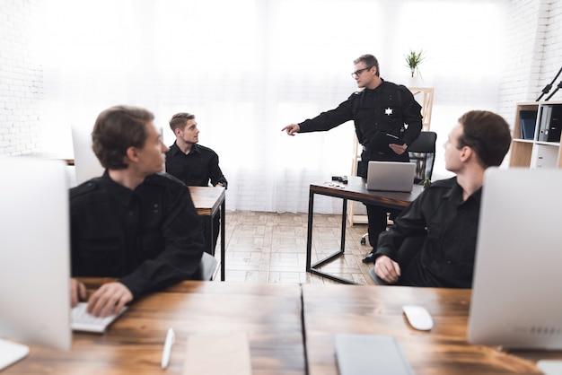 Politieagent instrueert de ondergeschikten in het politiebureau.