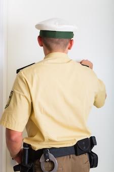 Politieagent kloppen op de voordeur van het huis