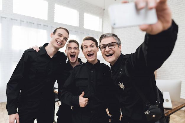 Politieagent maakt selfie met ondergeschikten.