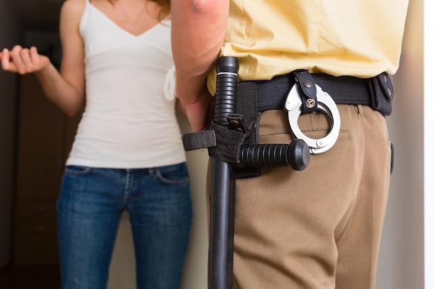 Politieagent ondervraging vrouw bij de voordeur