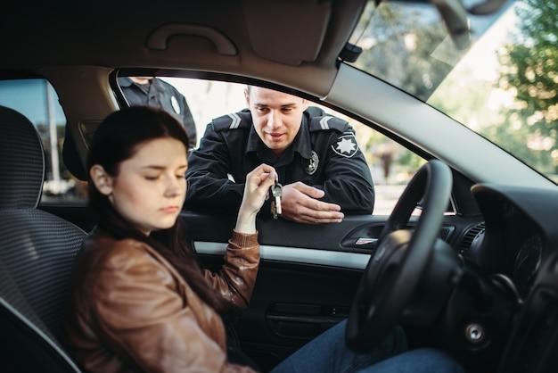 Politieagenten in uniform controleren vrouwelijke chauffeur