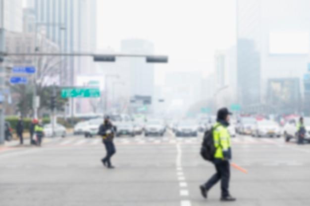 Politieagenten op de laan van de grote stad. autoverkeer op de kruising. vervaagd.