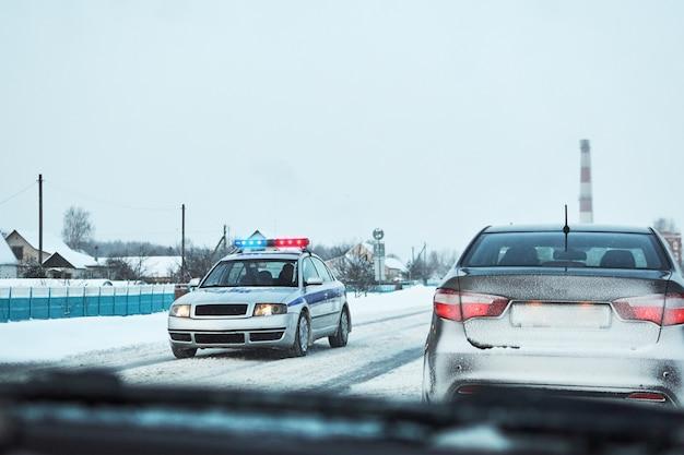 Politieauto met rode en blauwe flitslichten hield auto op de winter sneeuwweg tegen
