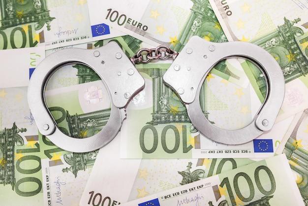 Politiehandboeien op eurobankbiljetten - concept van financiën en criminaliteit