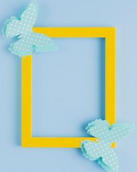Polka gestippelde vlinder op geel grenskader over blauwe achtergrond