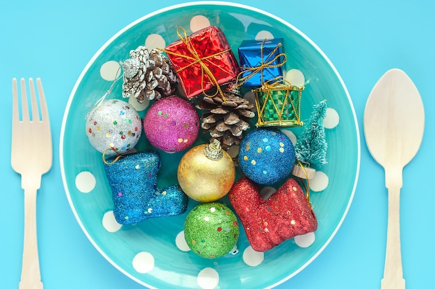 Polka-puntplaat van kerstmisornamenten met lepel en vork op blauwe achtergrond voor kerstmisdag
