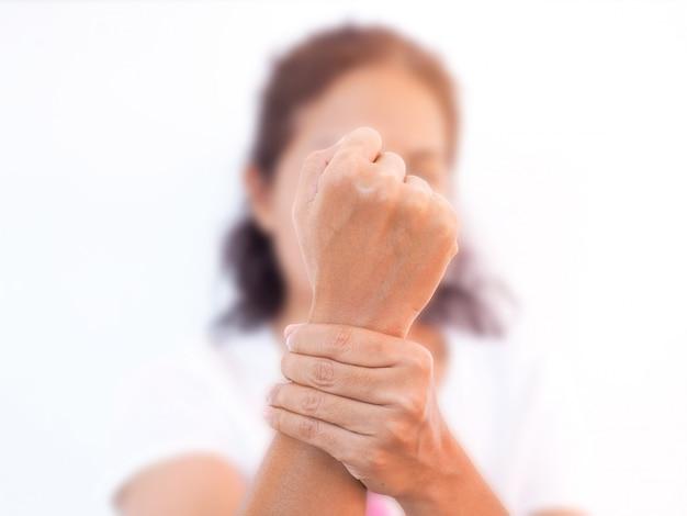 Polspijn door reumatologie en osteoporose van volwassen aziatische vrouw, botbeschadiging gewrichten van de pols met wazig gezicht.