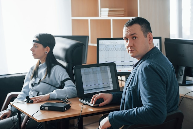 Polygraaf wordt getest. meisje passeert leugendetector in het kantoor. vragen stellen