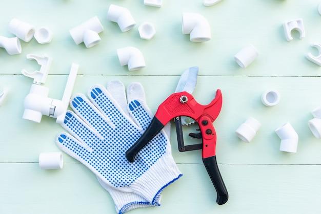 Polypropyleen buizen en koppelingen. handschoenen en een pijpsnijder op een blauwe tafel.