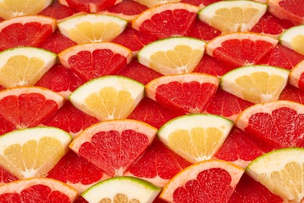 Pompelmoes en grapefruit sappige plakjes muur.