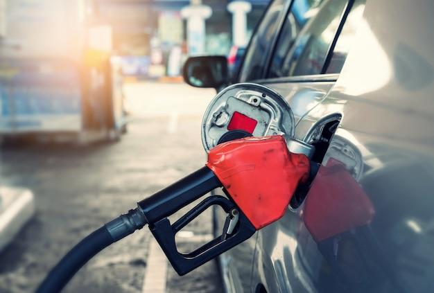 Pompende benzinebrandstof in auto bij benzinestation