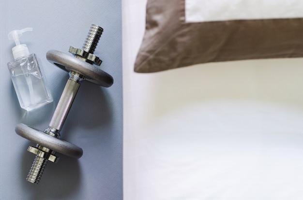 Pompende fles alcoholgel voor het reinigen van de hand na gebruik halter bij het doen van oefeningen in de slaapkamer om thuis te blijven om geïnfecteerd te beschermen tegen corona-virus.