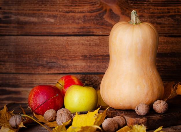 Pompoen, appels en walnoten op rustieke houten ruimte met ruimte voor tekst. thanksgiving en oogst