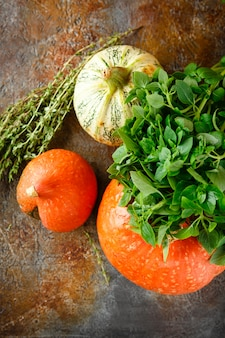 Pompoen, basilicum en tijm op een roestige tafel