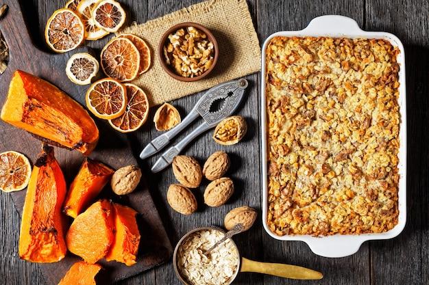Pompoen dump cake met traditionele pompoentaart kruiden: kaneel, kruidnagel, nootmuskaat met walnoten en gerolde haver bovenop geserveerd op een ovenschaal op rustieke houten achtergrond, bovenaanzicht, close-up