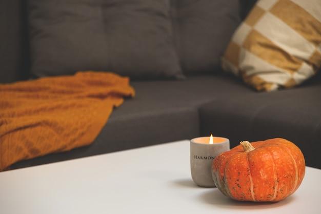 Pompoen en betonnen kandelaar op tafel in woonkamer naast bank met kussens en deken herfst...