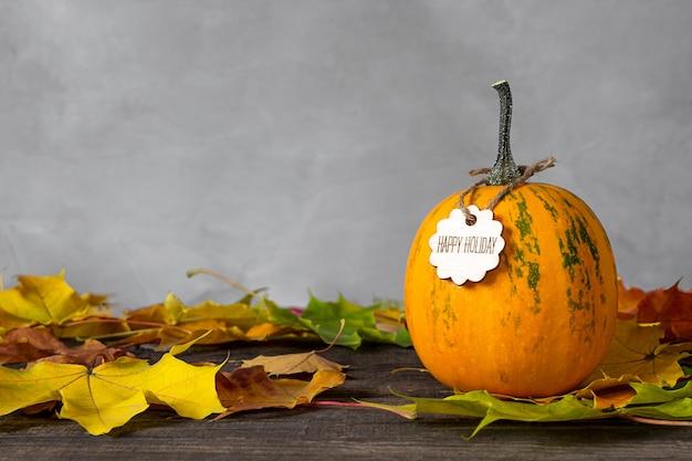 Pompoen en herfstbladeren op houten tafel.
